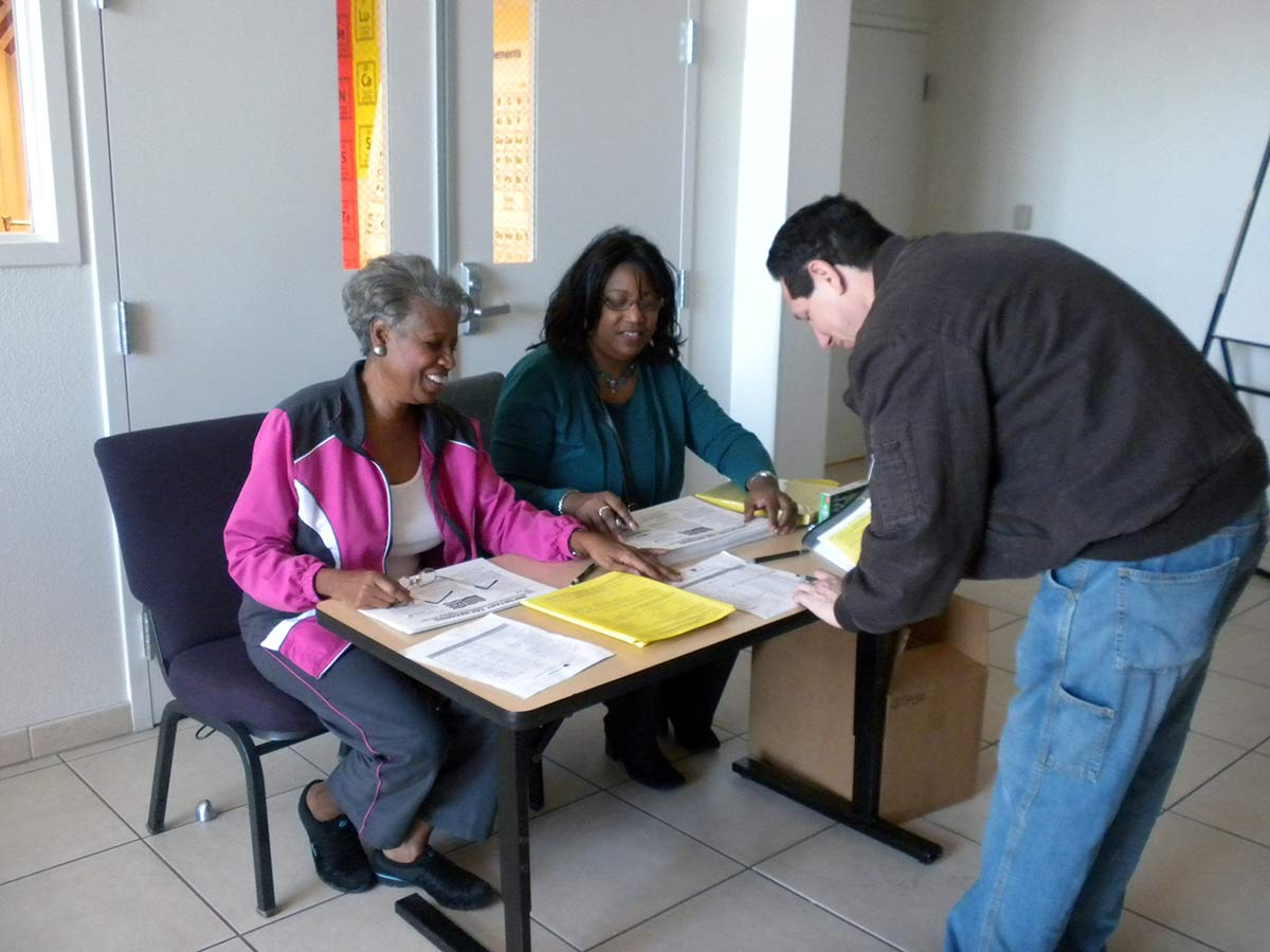Two female volunteers assisting a male tax payer sign in for tax preparation services