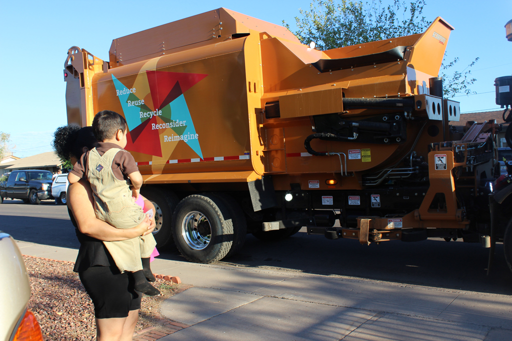 Mother and child watching garbage collection truck