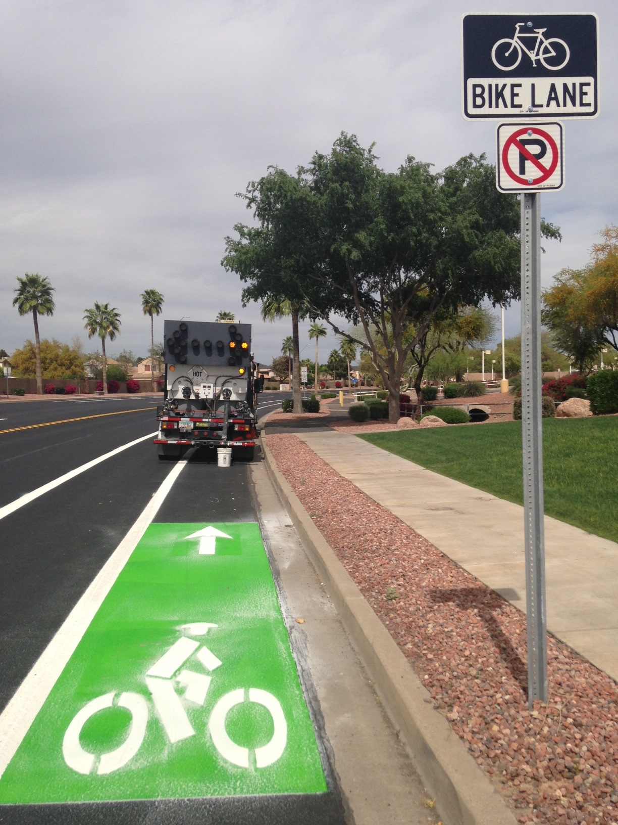 Green bike lane with white symbols being painted