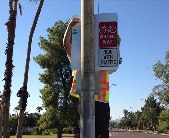Wrong way sign being hung on pole
