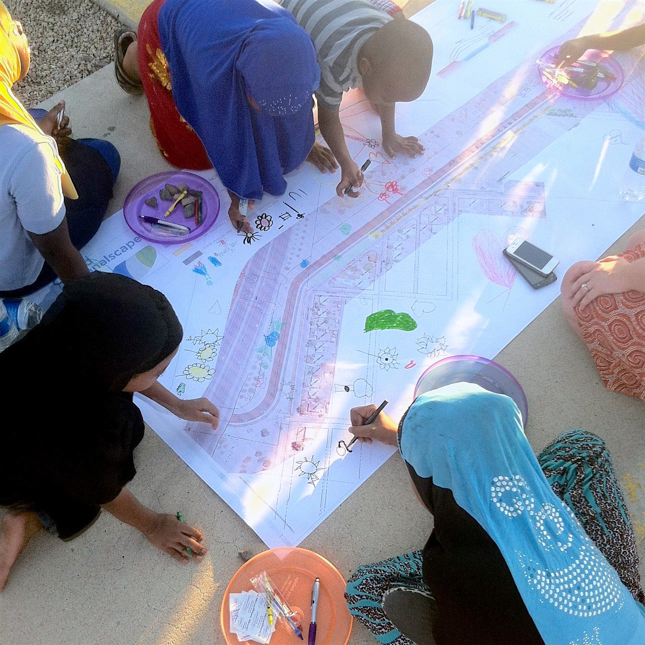 Children working on art project on ground